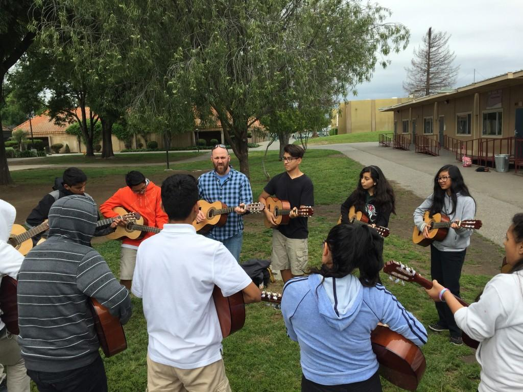 A circle of students and teacher playing the guitar.