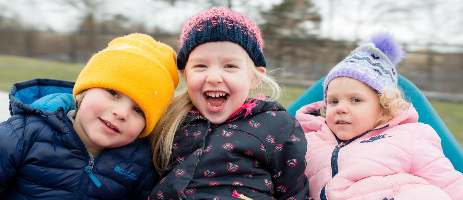 3 preschoolers on playground in their winter hats and jackets