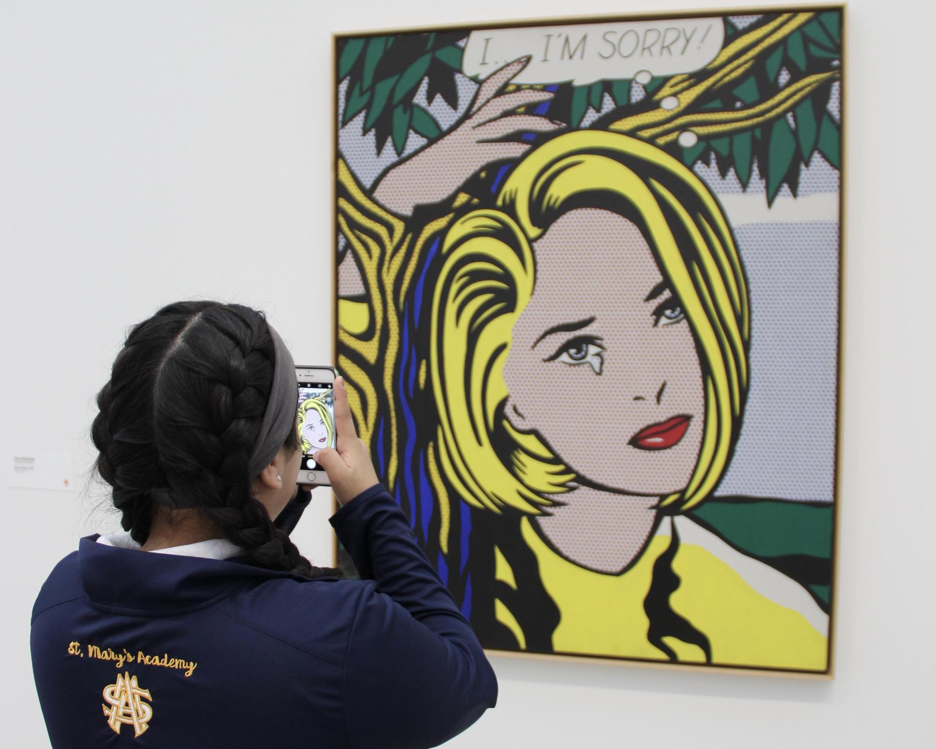 student taking a photo of a photo in an art museum