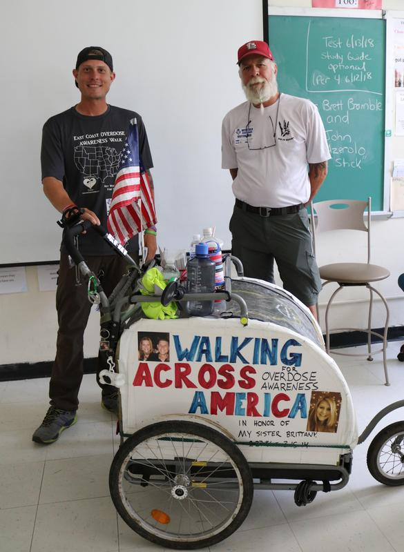Brett Bramble (left) showed students at Westfield High School mementos he's been given by people who have lost a loved one to a drug overdose.  Bramble and John Azerolo are walking from Key West, Florida to Calais, Maine to raise awareness about drug overdose prevention, addiction, and recovery.  They visited WHS on June 8.