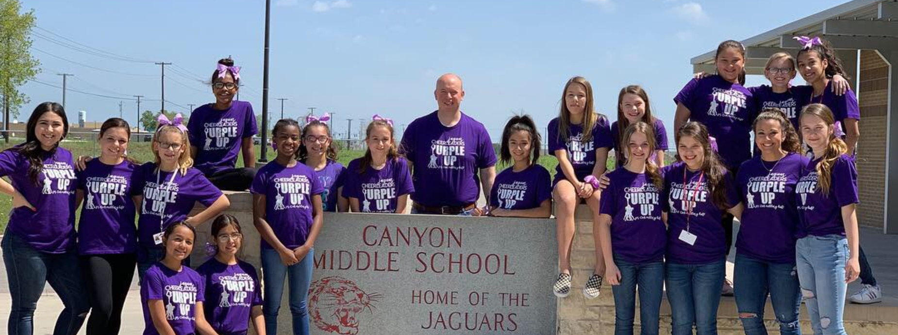 A group of girls with the principal, all in purple shirts.