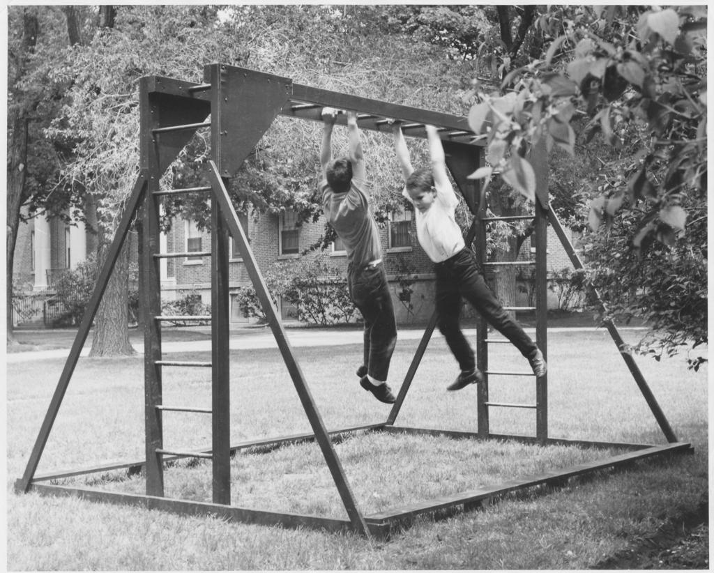 2 young students exercising on a wooden jungle gym