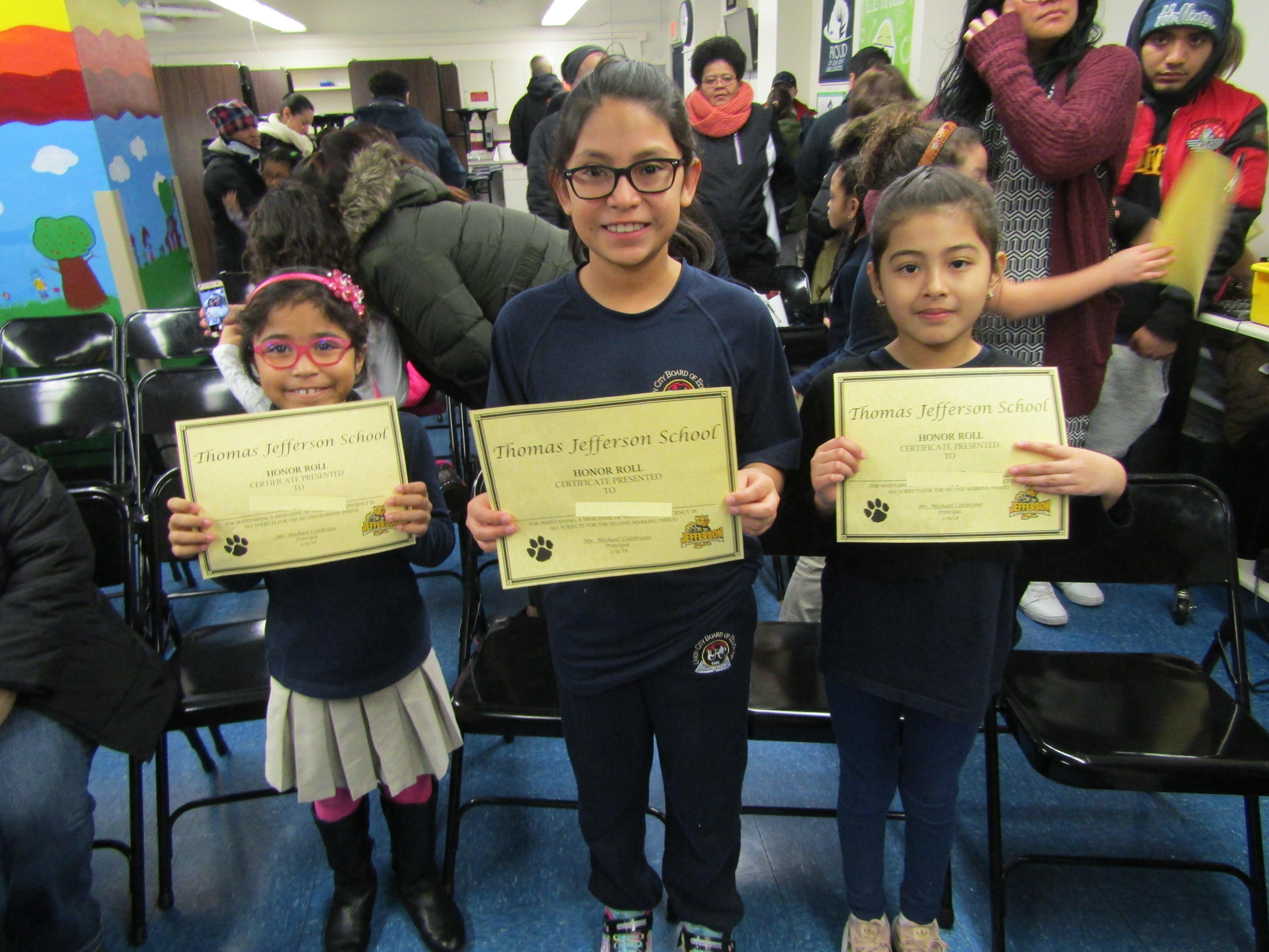 Three girls showing off their certificates of honor