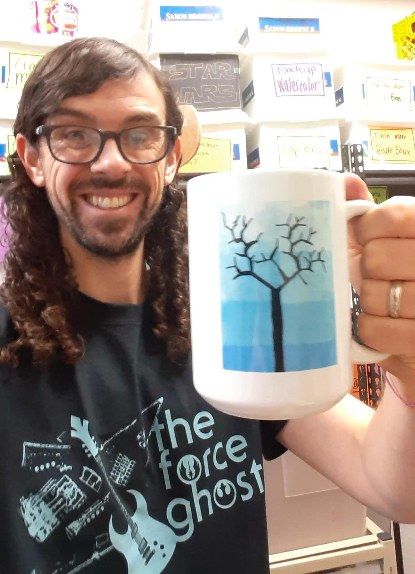 Mr. See holding an Original Works Mug