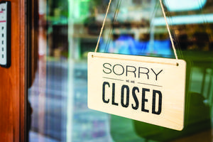 Sorry we are Closed sign in a glass door.