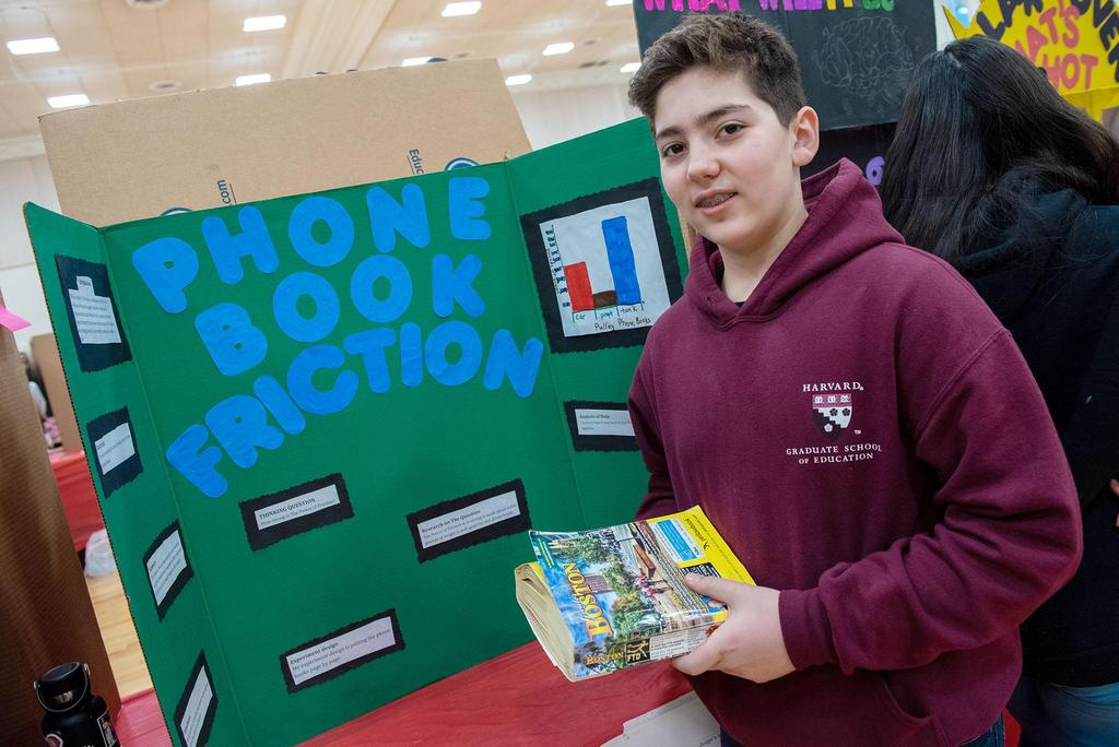 A student stands in front of his science fair project