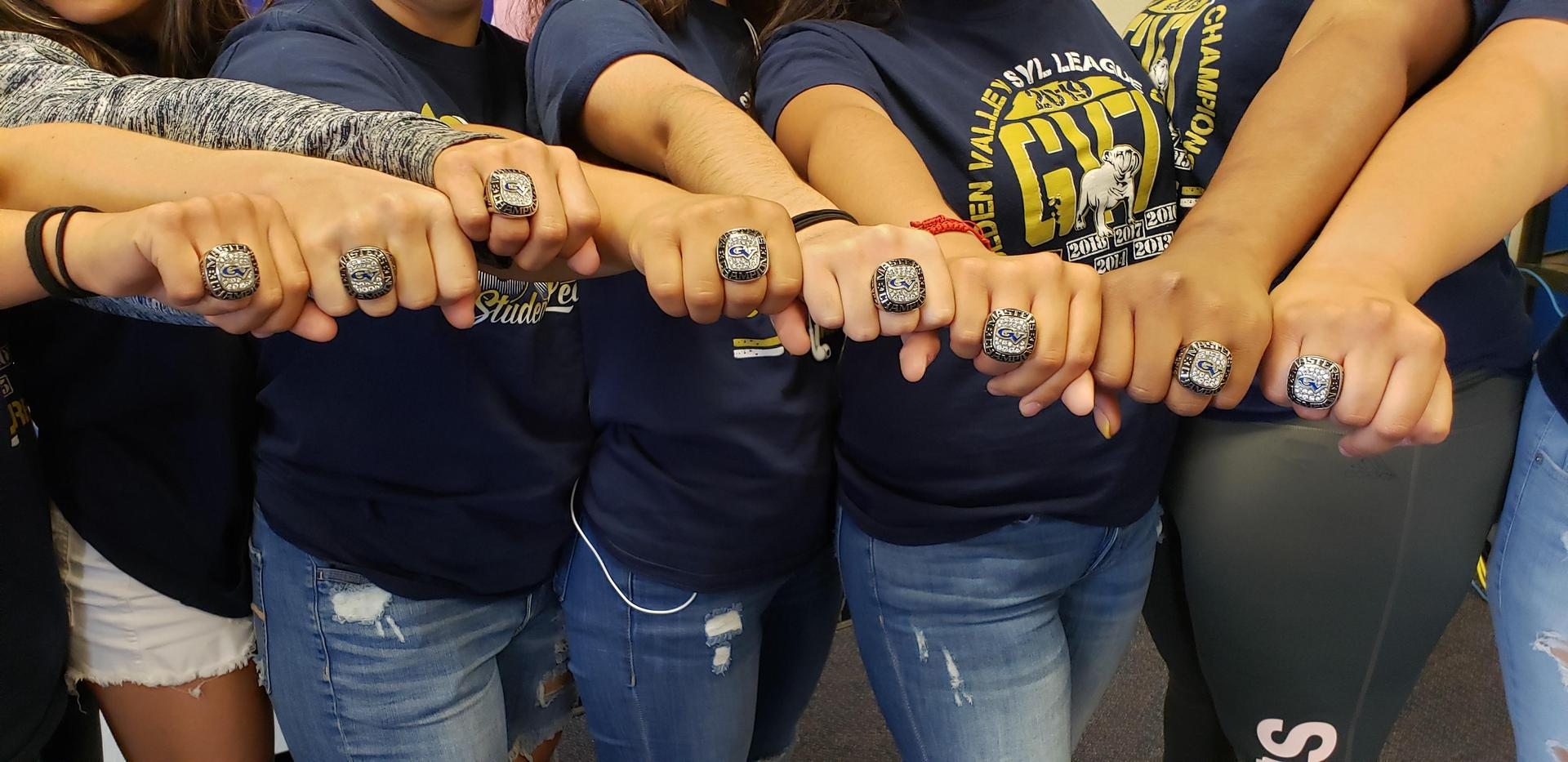 GV girls wrestlers showing their CIF Masters Championship rings