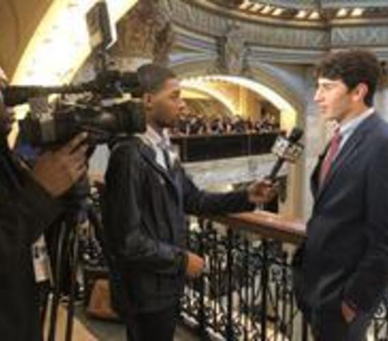 High school boy being interviewed by television news crew