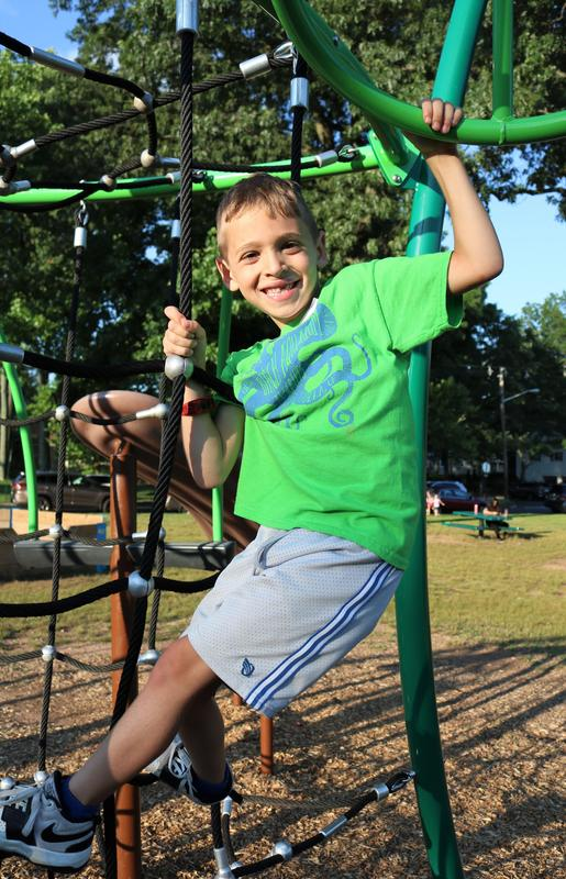 Jefferson School student enjoys playing on playground during Summer Social.