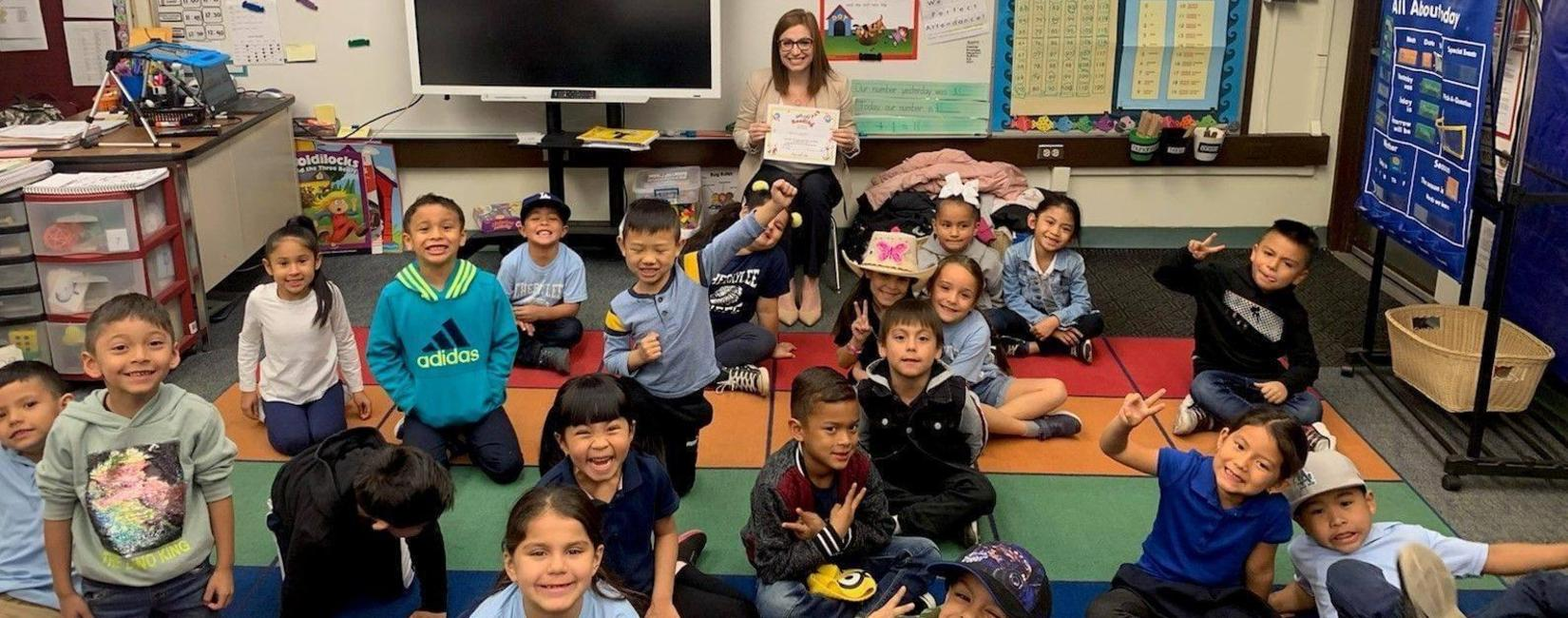 Assistant Superintendent Virginia Castro poses with students for group photo after read-along (photo from 2019)