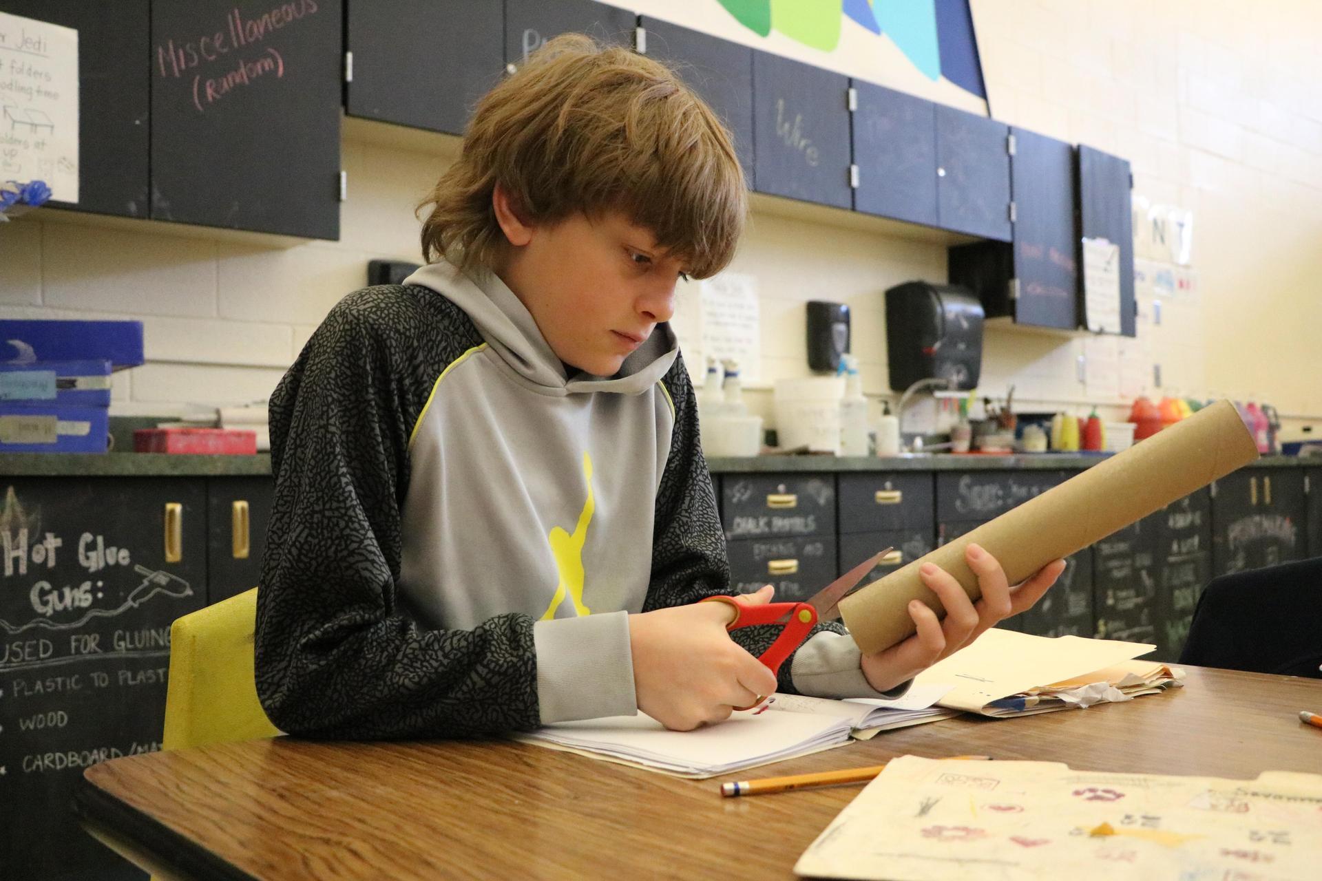 boy cutting cardboard
