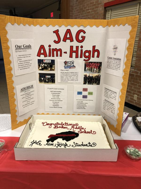 photo of the special made cake and a poster behind it; both promoting the JAG program and 2018 induction ceremony