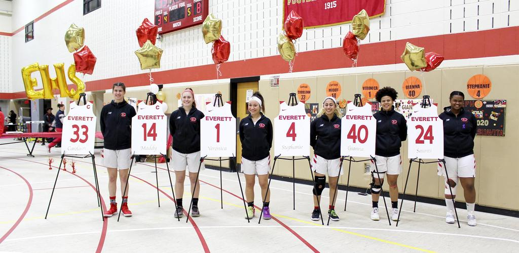 Senior basketball players with displays featuring their jersey numbers