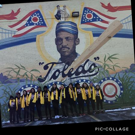 Picture of NSCW dancers standing in front of Toledo mural.