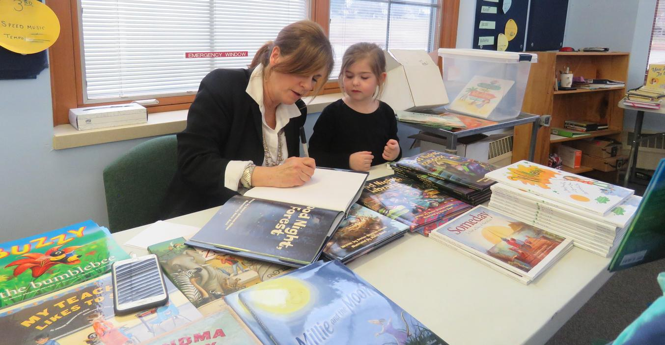 A guest author signs books at McFall's Literacy Night.