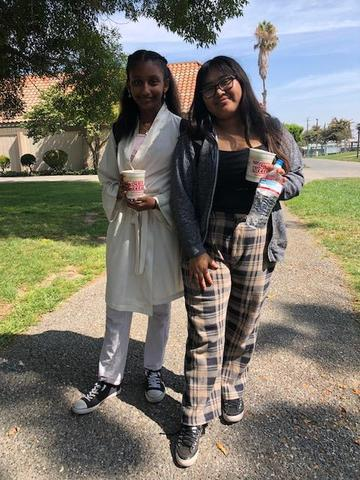 Two CCA students hanging out in their pajamas and eating cup noodles.
