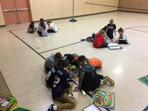 Three groups of students sitting in gymnasium playing board games.