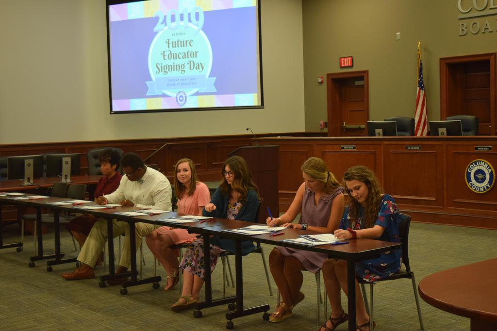 Students signing letters of committment at Georgia Future Educator Signing Day 2019 in the CCBOE board room