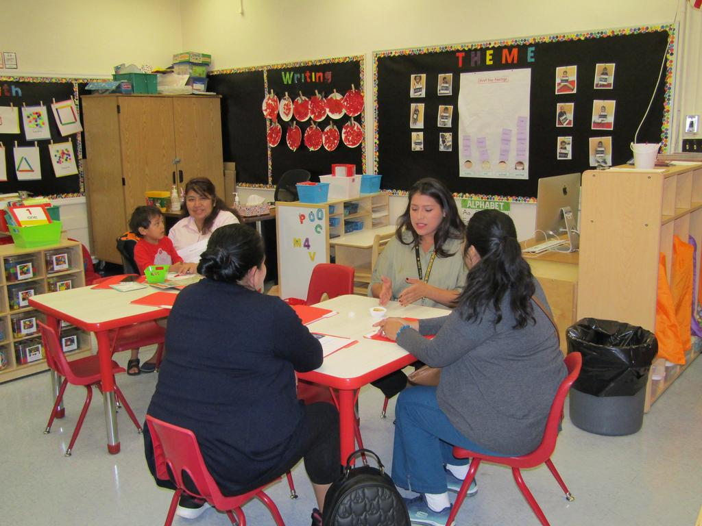 teacher seated at a table with parents talking together