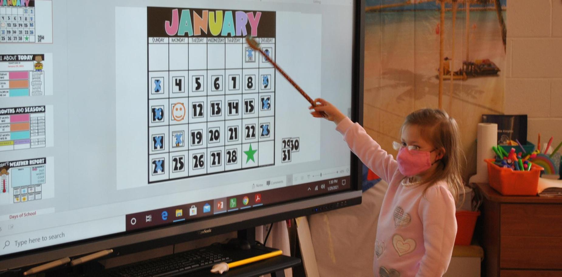 girl working at class smart board