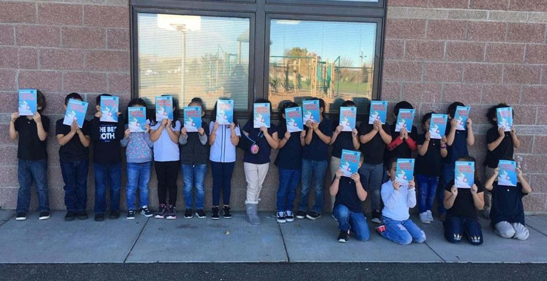 A group of kindergarten students with their donated scholastic books covering their faces.
