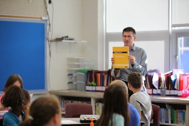 teacher holding book in front of class