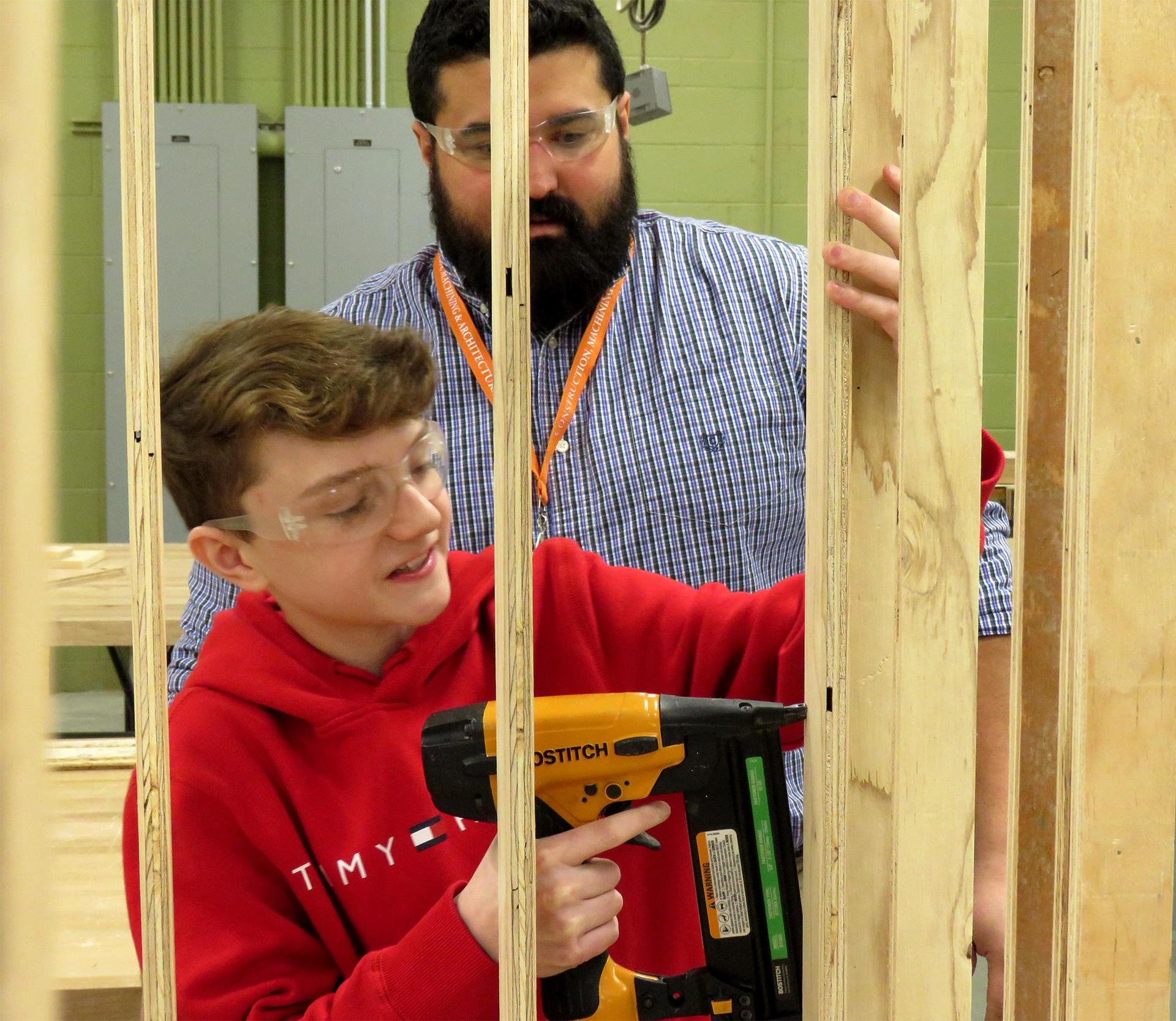 A student uses a nail gun under the direction of a teacher