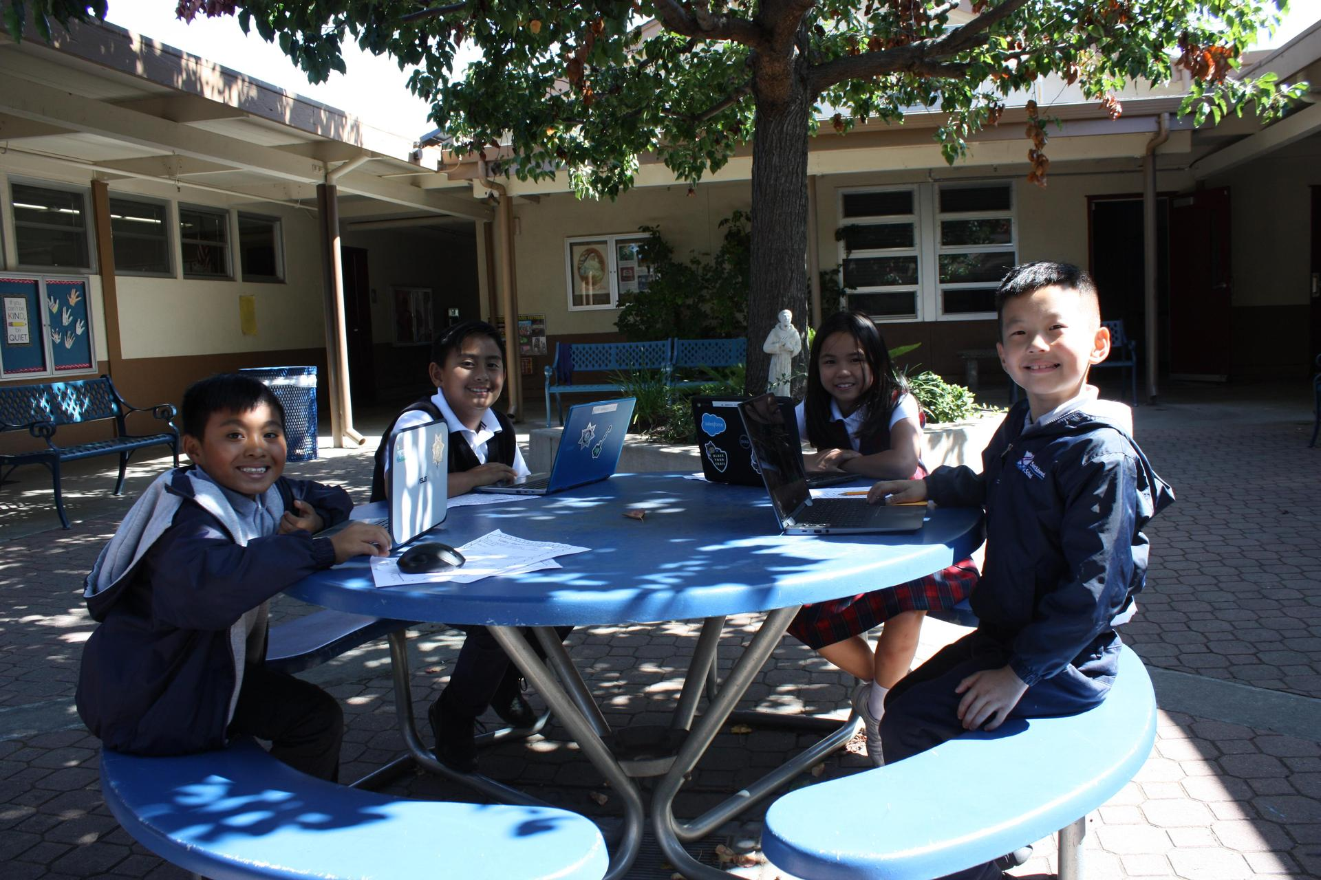 Students sitting at table with laptops