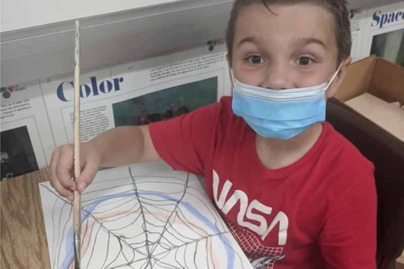 a student painting his spiderweb