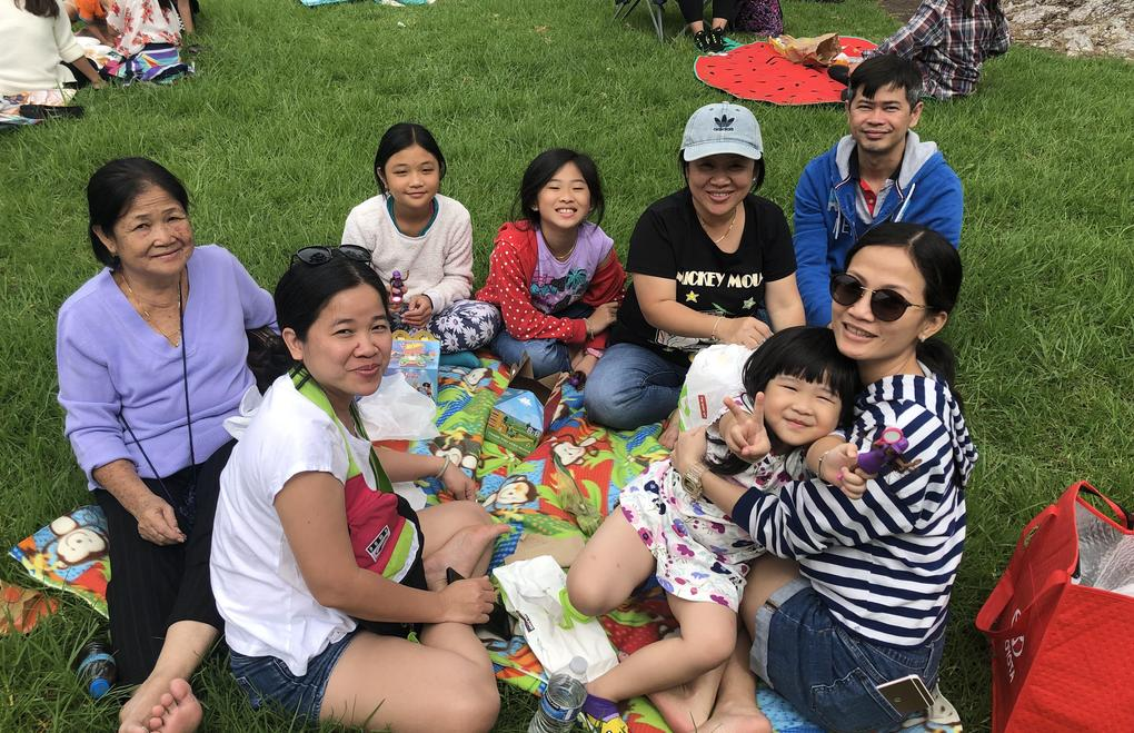 A family sits together on a blanket together having a picnic.