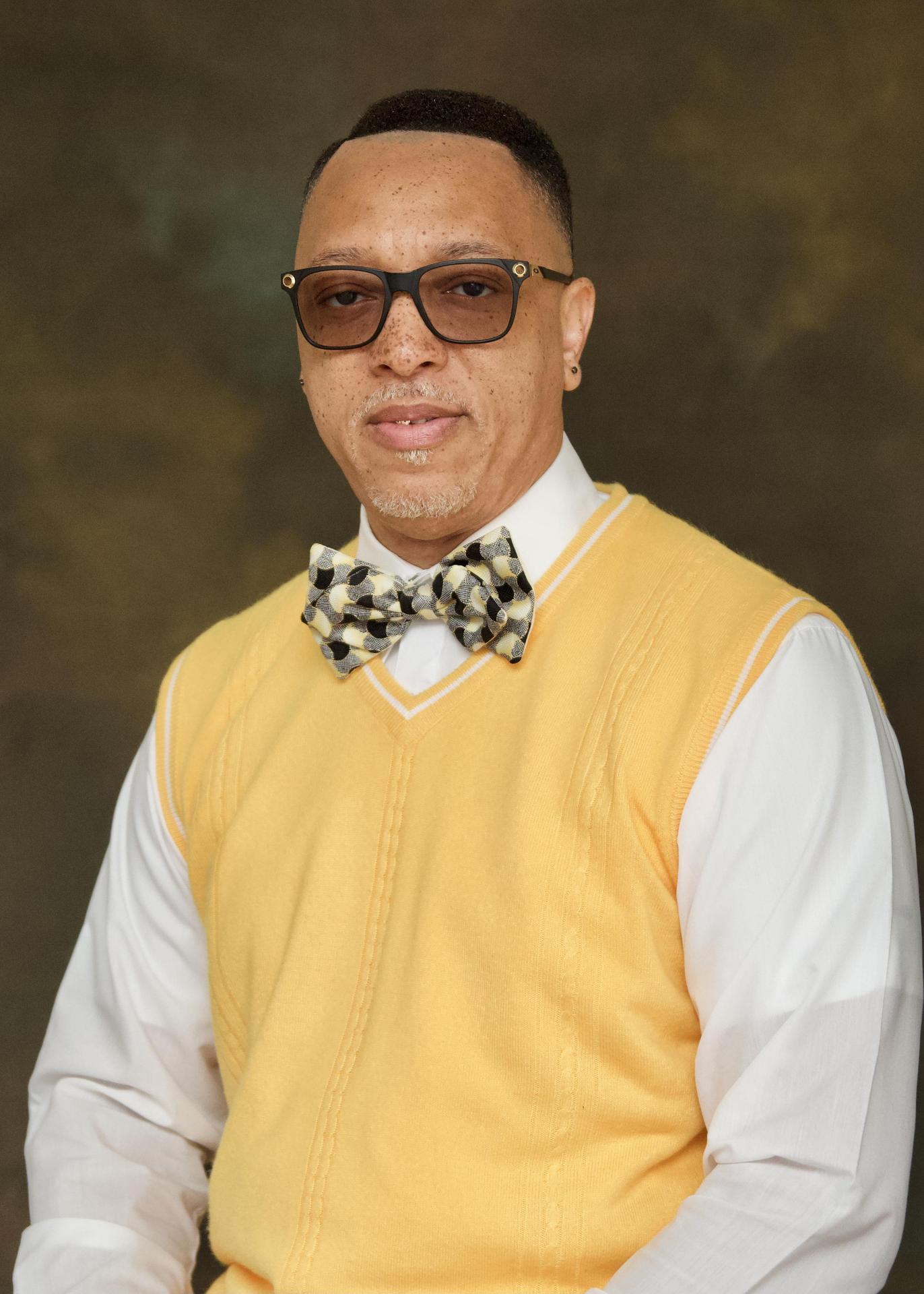 Mr. McKnight wearing a yellow sweater and glasses smiling.