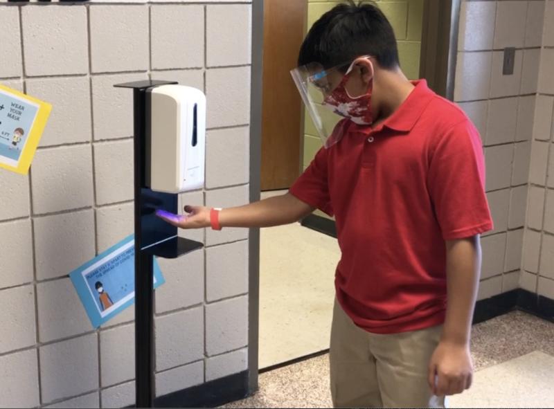 El estudiante se lava las manos con desinfectante.