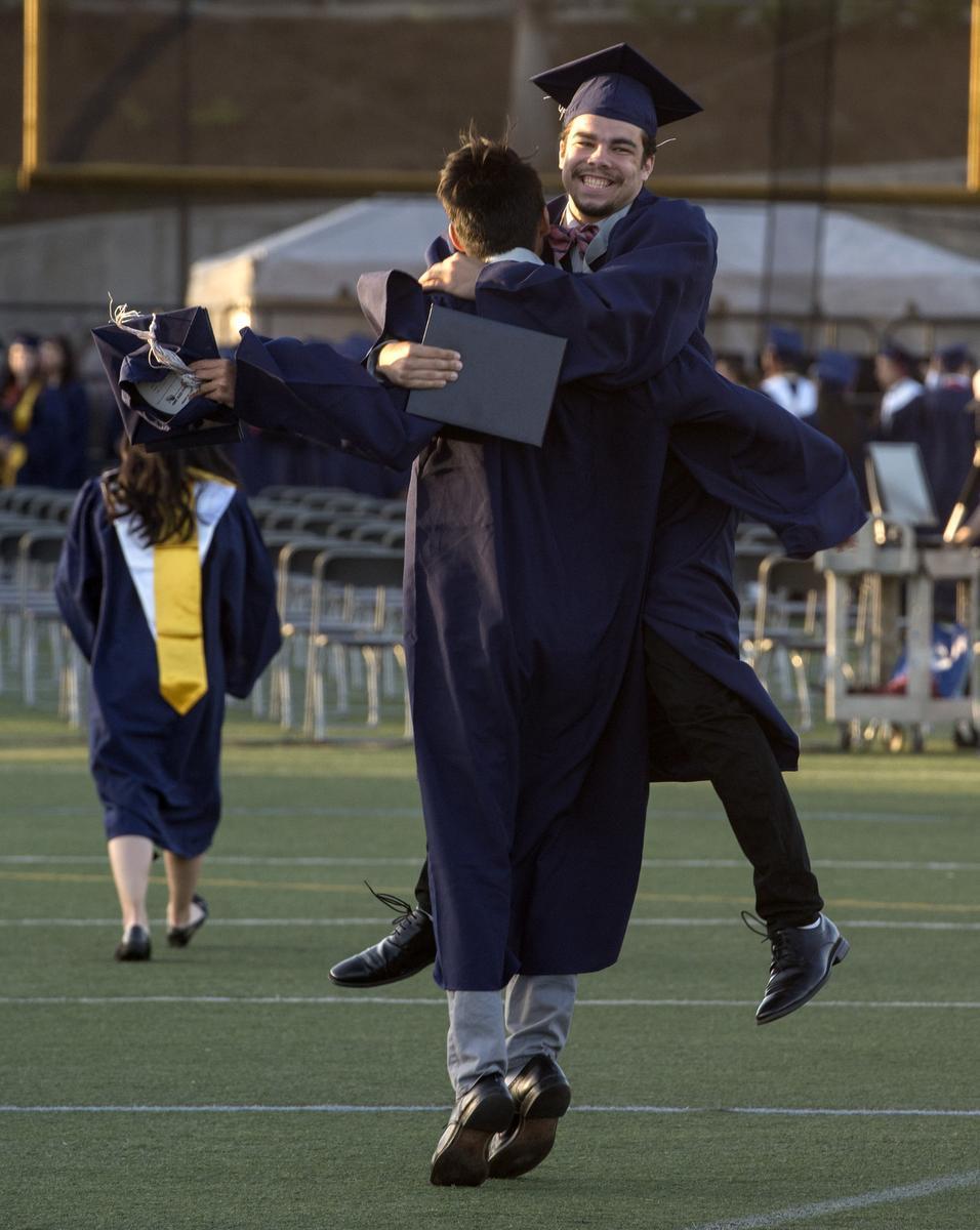 Two graduates hugging after graduation