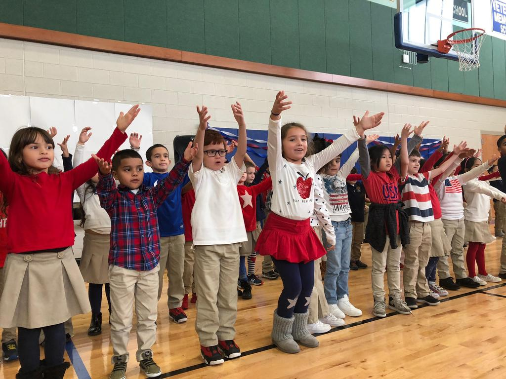 children singing for veterans with their hands up