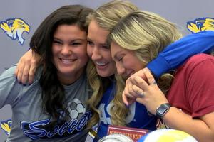 soccer players katelin Heise, Lexi Jackson and Kyler Carrasco hug after signing to play collegiate soccer