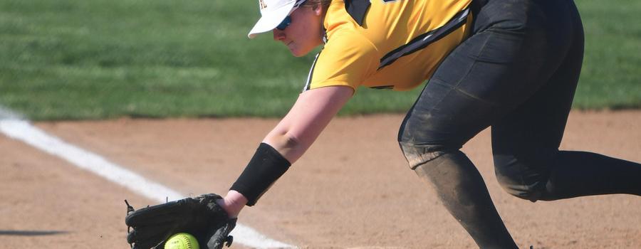 Girls varsity softball player reaching for a ball