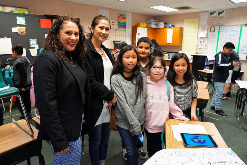 fifth grade teacher stands with mom and children at exhibition night