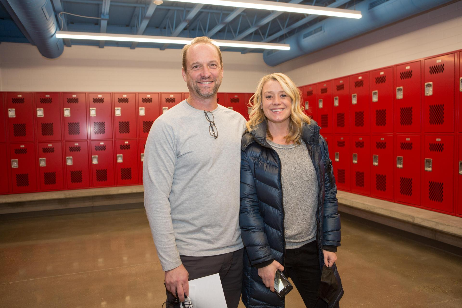 donors standing in football team room with red lockers behind