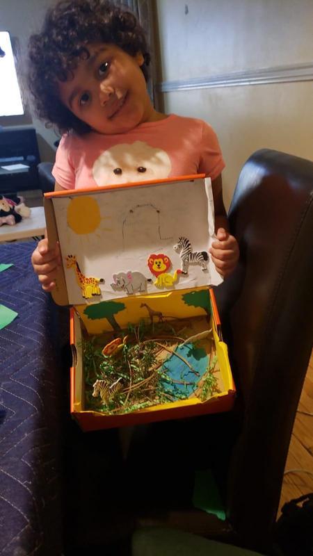 Student holding her habitat diorama