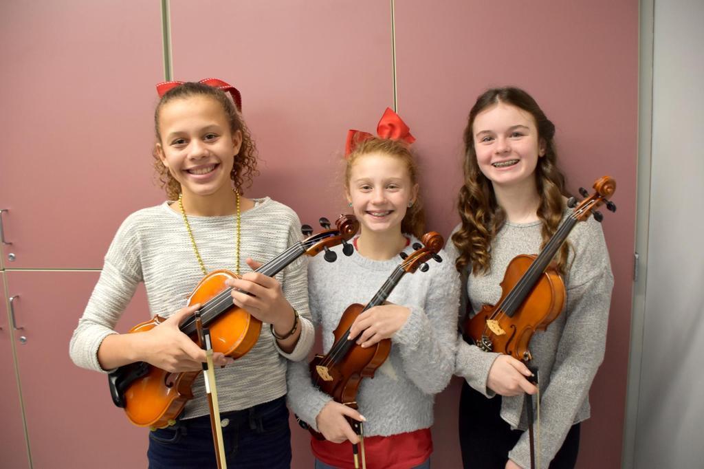 Three girls holding violins, backstage