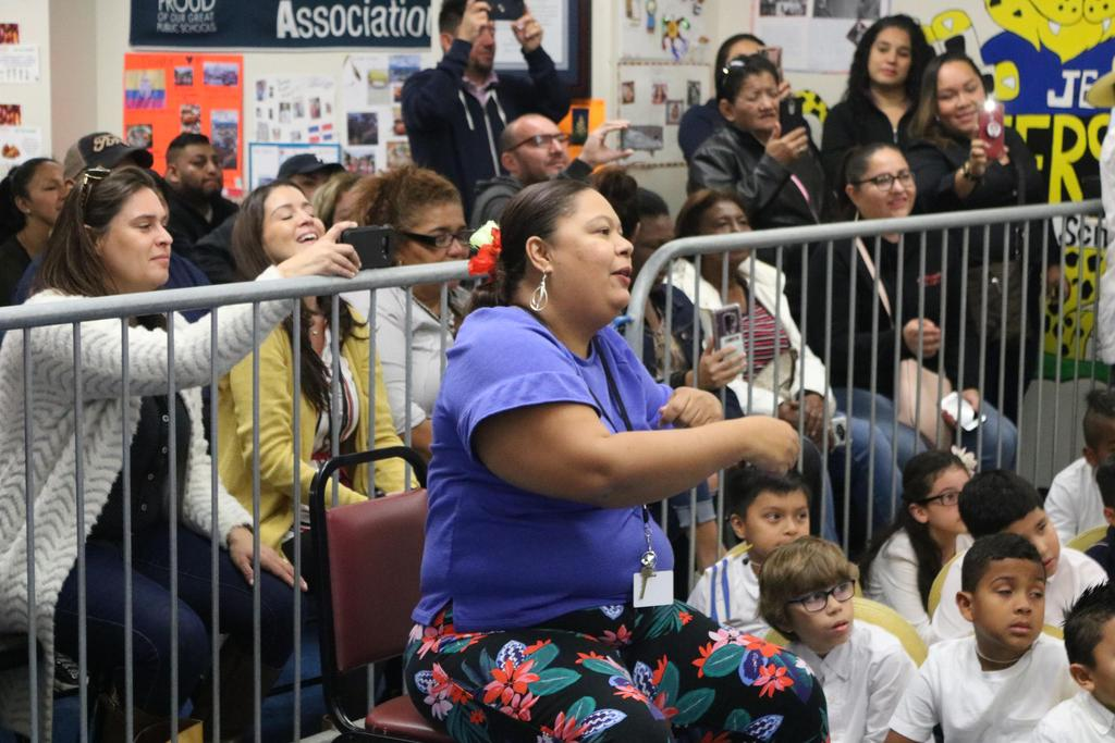 Mrs. Ramirez guiding the students performance with the parents behind her taking photos