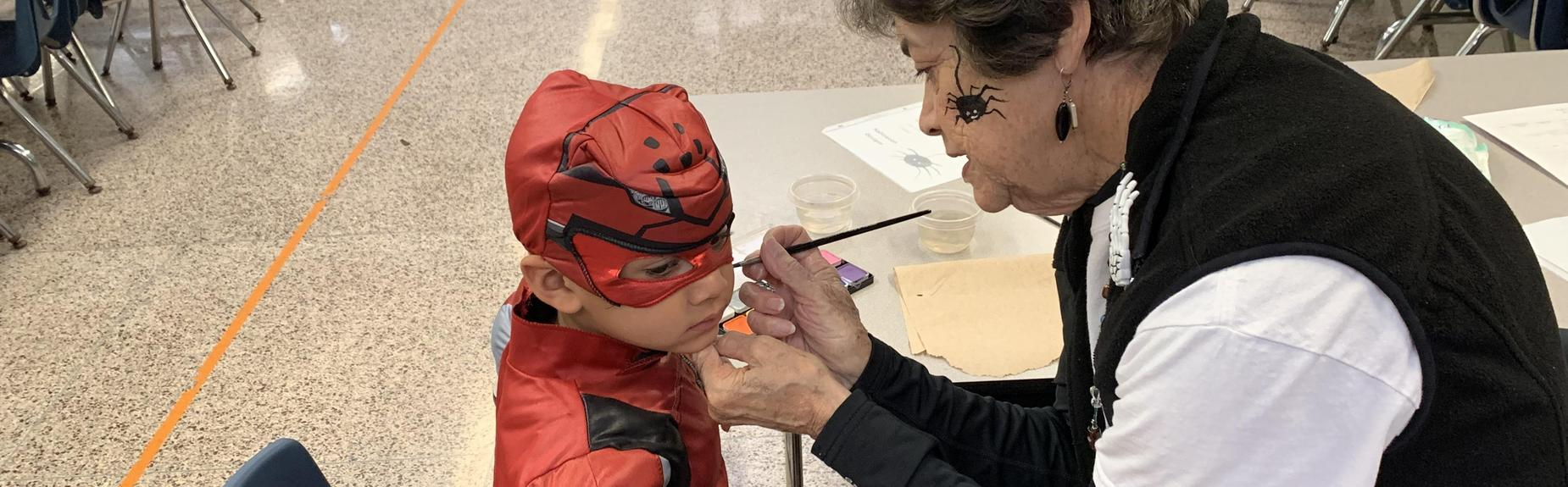Volunteer painting face at Fall Festival