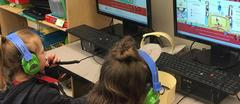 Two Elementary Students with headphones looking at their computer screens.
