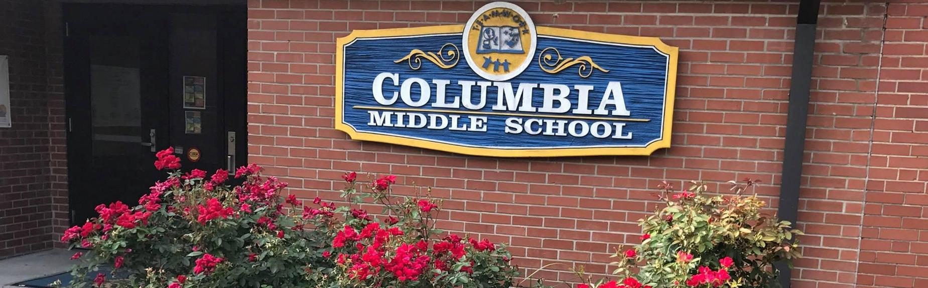 Columbia Middle School sign on wall outside and bushes
