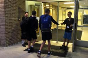 Two students greet kids as they come in the doors.