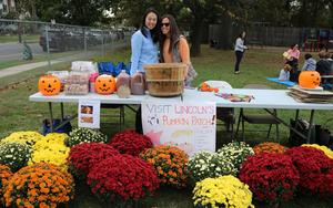 Photo of two members of Lincoln School PTO behind table selling mums, cider donuts and other fall fare at annual Pumpkin Patch.