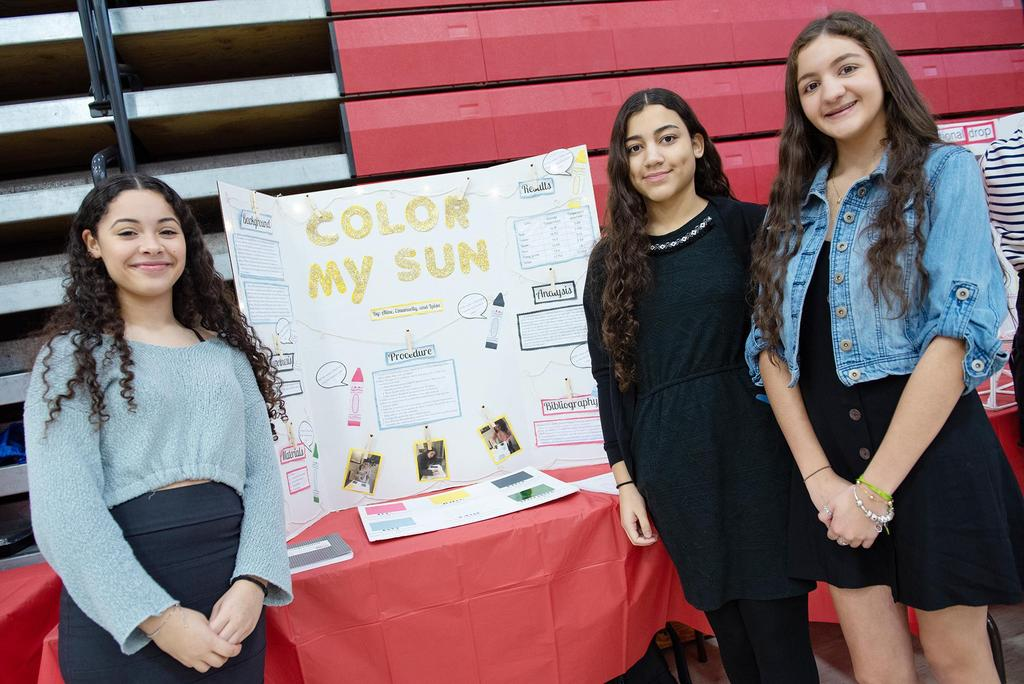 Three girls stand in front of their entry entitled Color My Sun