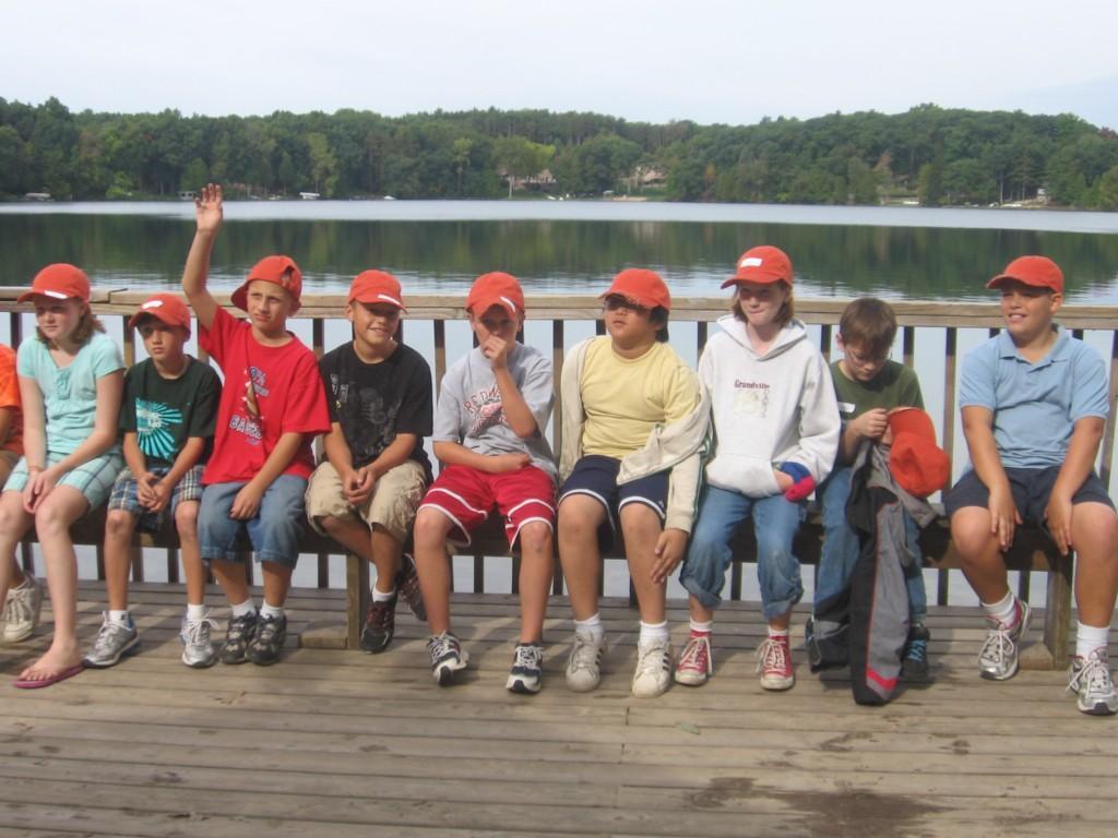 kids pose on bench by lake at camp