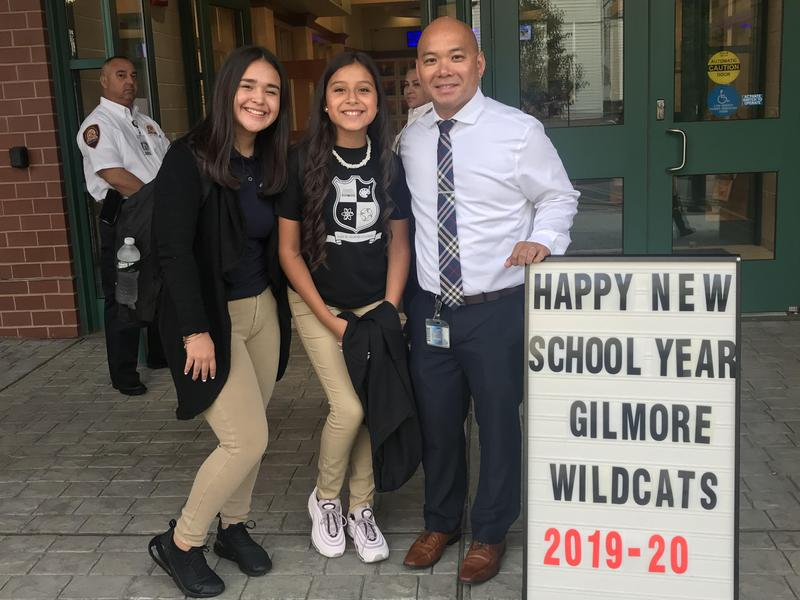 mr. pinzon with two girls at the entryway