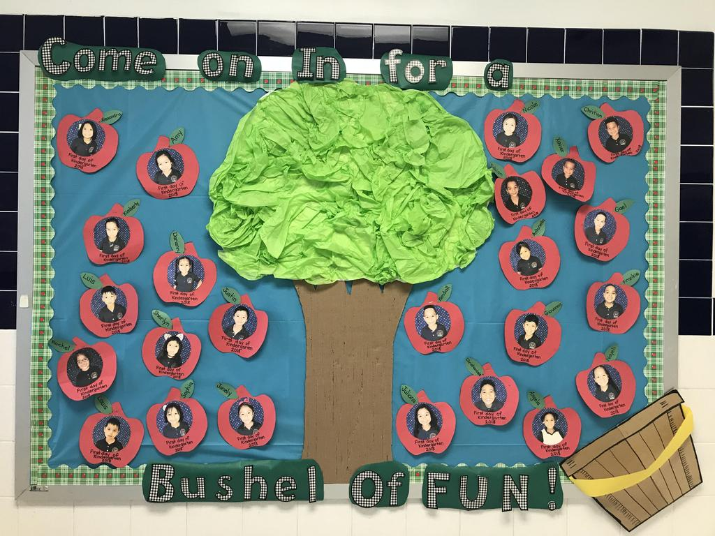 bulletin board display: Come in for a bushel of fun, apple tree with student pictures on apples falling into bushel